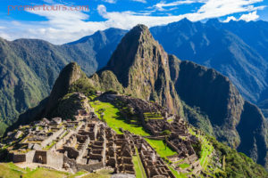 Machu Picchu with blue skies and green grass